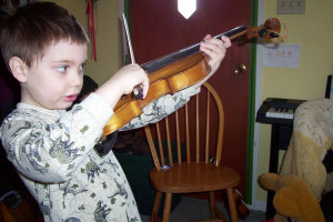 Child trying to play violin